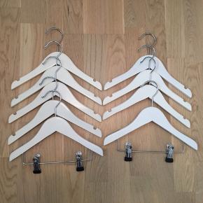 9 stk børnebøjler i hvidmalet træ, 7 alm bøjler og to med klemmer. Bøjlerne er købt i ILVA. Brugt men pæne, enkelte brugsspor på et par af dem. Afhentes i Gentofte eller sendes på købers regning.