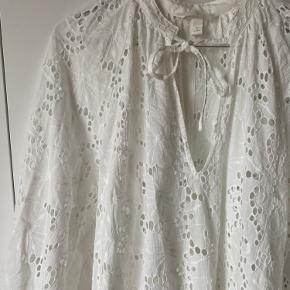 Utrolig smuk, lang hvid kjole med broderie anglaise fra H&M Conscious i str S. Aldrig brugt. Kjolen har lommer i siden, fint strammet ind ved hænderne og bindebånd ved halsen. UnderKjole medfølger ikke.