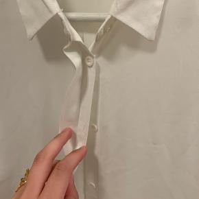 """Fin """"gennemsigtig"""" hvid skjorte, som er længere bagpå end foran. Da jeg ikke får den brugt, sælges den"""