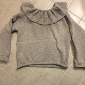 Smuk grå strik trøje med flæsekant. Str 3 men svarer til 92/98. Ingen fnuller, pletter eller andet der viser tegn på brug.