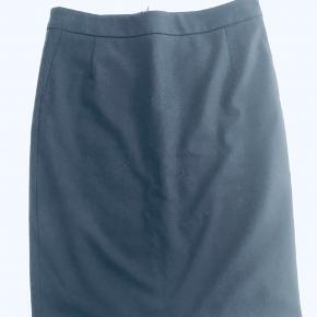 Mørkeblå 'pencil-skirt' m/linning, slids bagpå & lynlås samt indvendigt foer. Skrå-lomme effekt samt lommer bagpå a la habit-bukser Længde: 50 cm. Brugt få gange! Opbevaret i røgfrit hjem uden kæledyr.