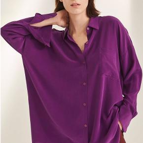 BIANCA POCKET SHIRT - PURPLE  Bianca skjorten er en klassiker fra Kokoon. Denne er med en brystlomme, lange ærmer med brede ærmelukninger og et lige snit med en anelse længere ryg. Den flotte lilla farve lyser op og fungerer godt både til fest og hverdag.