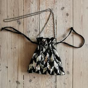Cool sort og sølv paillet fest taske med lang kæderem og snoretræk, der fungerer som både lukning og hanke (så man kan vælge at putte kæderemmen i tasken og bære den i hånden vha. snorene istedet).   Stand: Helt ny. Aldrig brugt.   Pris: 350kr