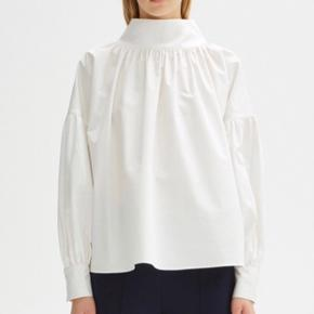 BYD!!!  Kan prøves i Magasin ;)  Rodebjer Kellman Cotton is a crisp cotton blouse with a loose polo neck. The blouse has a loose fit with long sleeves.  Str L/40 Aldrig brugt