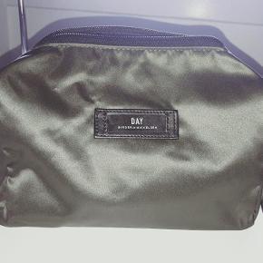 Ubrugt Day beauty (toilet)taske i mørkegrøn satin. Farven hedder pineneedle. Første billede af tasken gengiver farven bedst. Mål: 24 x 14 x 11.5 cm