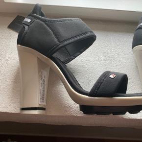 Helt ny Tommy Hilfiger sandal/heels. Super flotte på, men jeg får dem ikke brugt, så nu tænker jeg en anden kan have glæde af dem. Hælen er 10 cm bag på, og der er en smule plateau foran. De er sorte og nyprisen er 900 kr