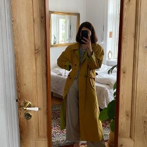 Fineste trenchcoat i gul med grønt inderfoer. Fin stand. Fitter onesize.