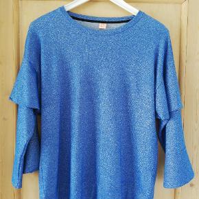 Smuk blå bluse med glimmer og brede ærmer.