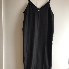 Enkel sort kjole med spagetti stropper og v-udskæring.  Stropperne kan reguleres. Længde fra udskæring ca. 100 cm Ren polyester.