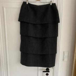 Super midi nederdel med 4 etager og slids bag Kvaliteten er helt i top Størrelse: Normal 42 Kun brugt få gange Ingen brugstegn