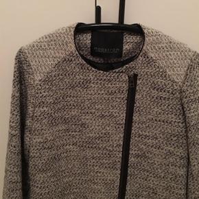 Frakke i grå-sort. Længde: 80 cm. Bredde under ærmet fra søm til søm: 47 cm. Ærmelængde fra ærmegab, ikke fra skuldersøm, 48 cm.