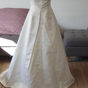 Brudekjole.  Smukkeste brudekjole belagt med perler og sten. Str xs/34, med langt flot slæb.  Kjolen er ikke renset.  Prisen er sat derefter, den fejler intet.