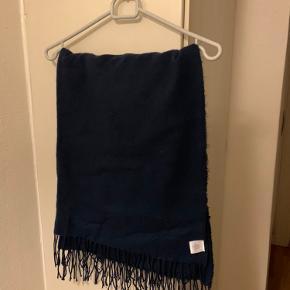 Stort mørkeblåt / navy Unisex halstørklæde fra Urban Outfitters. (Kan nok også bruges som sjælevarmer / sjal - se mål) Mål: længde uden frynser 180 cm og med frynser ca 200 cm. Bredde ca 80 cm. Materialet er ultrablødt 'acryl'. Nypris 280 Det her r brugt og vasket EN gang! (Har det også et ubrugt navy og et i lysegråt til 80 pr stk - se evt andre annoncer)