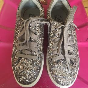 Glimtende grå sneakers fra Petit by Sofie Schnoor. Det er en børnesko str. 37 og svarer nærmere til 36 for voksne. Kun brugt én gang. Har plet i hælen. Bytter ikke.
