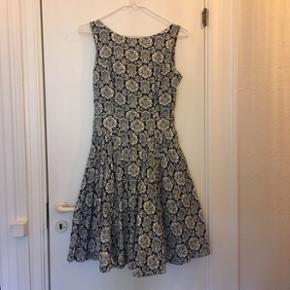 Kjole i smukt print med fastsyet bindebånd i taljen, lynlås bagpå og fuldt cirkelskørt.  Kun brugt få gange.