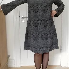 Bytter ikke. Eksklusiv porto.  Flot, enkel og elegant kjole, til fest med mere fra Gai & Lisva str. 36. Kjolen kan bruges til fest, hverdag mm. Kjolen har grå bund og et fint sort mønster. Ærmer med trompet effekt, som giver kjolen et smuk feminint udtryk. Har en lille slids i nakken, lukkes med en hægte. Størrelsesguide for en str. 36: Bryst mål 84 cm Talje mål 68 cm Hofte mål 94 cm For og bag målt stykket ved bryst linen, 96 cm. Længde fra skulder og ned 96 cm. Omfang rundt forneden 136 cm. Modellen på billederne er en str. 38/40. Højde 167 cm. 100% Viskose. Kjolen er ny. Hænger i dragtpose. Kommer fra et ikke ryger hjem.