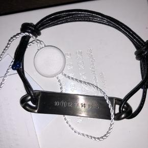 Super lækkert og tjekket armbånd i sort læder og flerfarvet metal fra luksuriøse franske MAISON MARTIN MARGIELA. Armbåndet kan justeres til flere slags håndled og designet er unisex. Købt i butikken i New York og kostede 1.900kr. MADE IN ITALY