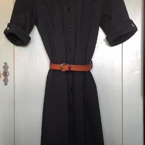 Skjortekjole fra Soaked in Luxury. Størrelse M. Jeg har brugt den en del, så den er godt gået til. Fejler intet, men farven er ikke knivskarp sort længere. Godt 70'er udtryk, synes jeg.  Bæltet følger ikke med, men næsten hvilket som helst bælte (som ikke er for bredt) kan bruges. Det oprindelige bælte har jeg ikke mere.  Jeg har i tidernes morgen klippet mærkatet ud af kjolen, så jeg kan ikke redegøre for metervaren – men en lækker bomuldslærredssag.  Pris: 150 kr.  -- OBS: Tradono beskærer ofte mine billeder, så jeg må desværre henvise til DBA for billeder i fuld størrelse, suk --  Handler helst via. MobilePay. Bytter ikke.  Rabat ved køb af flere af mine varer.  Kan afhentes i postnummer 9541 eller sendes til nærmeste GLS-udleveringssted for 39 kr.