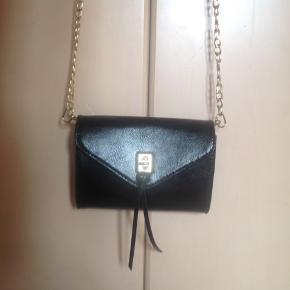 Smart sort Lille taske. Den kan bruges over skulderen eller sættes fast i et bælte, som en bæltetaske. Tasken måler 18 x 15 cm med en lænke/rem på 128 cm.  Indvendig er der to større rum, et mindre rum med lynlås og plads til 3 kort.