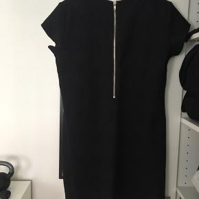 Løst siddende kjole i slangeskindspræget stof. Lynlåsdetalje på ryggen.