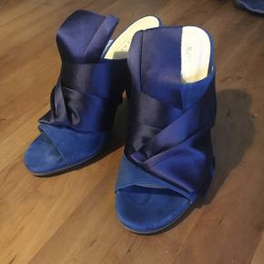 """Ny pris! Sælger mine Notabene Cher. Nypris 2.495 kr. Højhælet slip-in sandal i mørkeblå ruskind med en dekorativ navy satindetalje """"bundet"""" om forstykket på skoen samt en chunky hæl. Aldrig brugt, kun prøvet i butikken. Kan også bruges af en str. 37"""