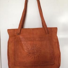 Super cool orange vintage taske med marokkansk grafik præget ind i skindet. Den er lavet i blødt kamelskind og er foret indvendigt. Tasken foldes for at lukkes, men har også et lynlås rum. Den bæres på skulderen eller i hånden. Kom med et bud.  Varen befinder sig i 9520 Skørping. Sender med DAO.  Se også min øvrige annoncer. Jeg sælger tøj, sko og accessories. Pt er min shop fuld af vintagekup, high street fund og mærkevarer i mange forskellige str. Kig forbi og spøg endelig!
