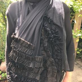 Du finder ikke et tørklæde /sjal magen til !Fantastisk smukt stort sort gennemsigtigt tørklæde /sjal med flæser fra Ivan Grundahl. Rå kanter som kun Grundahl kan... Mål ca 200 cm x 120 cm Kan bruges til hverdag og fest Jeg gav ca 2000 kr for det for mange år siden , har kun brugt det til 2 fester . Ellers har det ligget i en pose i skuffen. Materialemærket er desværre faldet af, men stoffet er tyl-agtigt med stretch, ingen fejl /mangler Sælges for 750 kr