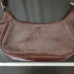 Meget anvendelig tæske i læder fra Aura. Farven er mørkebrun med lidt bordeaux nuance. Velholdt, fejler intet, har bare for mange. Prisen er plus porto.