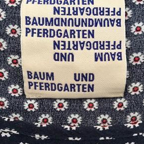 """Skøn kjole i mørkeblå med små hvide blomster. Lommer i siden, der giver et casual look. Snittet i ryggen gør, at den falder rigtig fint og giver lidt facon, så den ikke bare går """"lige ned""""."""