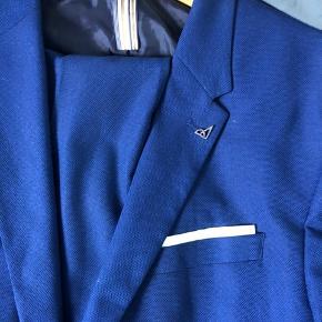 Smuk blå habitjakke inkl matchende buks fra Zara. Købt i Madrid i 2019 og brugt én gang. Sættet har mange lækre og unikke detaljer se fx den tilhørende nål, og den har et klassisk elegant slimfit snit. Jakken er i størrelsen EU 50 svarende til standard L og buksen er EU 40/ US 31. Nypris 1100 kr