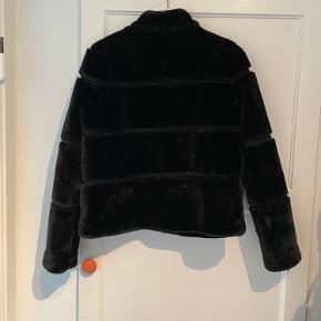 Mærket inde i jakken er kun syet i den ene side og sidder derfor løst