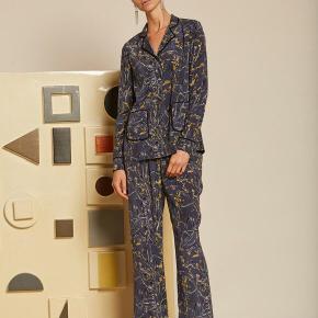 Fin manso silkeskjorte fra Julie Fagerholt Heartmade i 93% silk og 7% spandex. Kun brugt engang og i flot stand uden huller , pletter , fnuller eller lign, Brystmål: 51 cm på tværs fra armhule til armhule (dvs 102 cm i omkreds). Længde: 71 cm fra nakken og ned. Nypris: 2000 dkr Søgeord: skjorte silke silk shorts pyjamas print blomster blomstret mønster mønstret gul blå grå sort top sommer bluse.