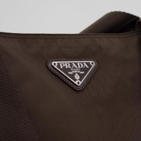 Prada Dark Brown Nylon Shoulder Taske   The iconic Prada nylon bag in dark brown, features one inner ziplock pocket, monogrammed lining, Saffiano leather trims & comes with the original authenticity certificate card.  - Line: PRADA - Made In Italy - Estimated Year of Design: 1990's  Details:  - Zip Lock Closure - One Inner Zip Lock Pocket - Monogrammed Lining - Comes with the original Authenticity Certificate Card.  Measurements:  - Hight 33cm - Width 40cm - Depth 13cm - Straps 60cm
