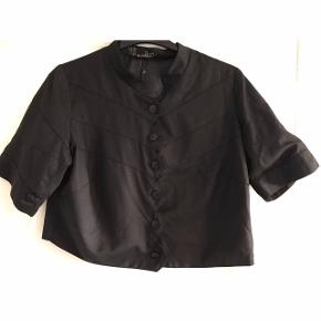Str. M i storpigestørrelse. Kort jakke med glat foer. Brystvidde: 59 cm. X 2. Længde: 55 cm.