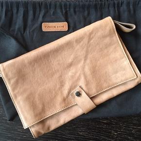 Smuk clutch, der er helt ubrugt, og har været pakket ind i medfølgende stofpose.   Materialer er læder og i en flot helt lysebrun farve.   Nypris: ca. 2700 kr.  Pris: 500 kr.