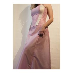 Todelt gallakjole med nederdel og corsage.  Corsagen er med snører i ryggen, og størrelsen kan dermed varieres.  Nederdelen er med lille slæb, men kan draperes bagpå, se billede to.  Begge dele er skræddersyet  Samlet pris 600 kr.