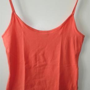 Varetype: Lille orange top med tynde stropper Farve: Orange  Lille orange top med tynde stropper og god udskæring i 95% bomuld og 5% elastan i str. L. Måler over brystet 86 cm. - uden at trække i stoffet. Længden er 56 cm. Aldrig brugt. BYTTER IKKE!