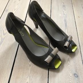Rigtig fin stilet i armygrøn/brun læder. Limegrøn og cafe latte farvet skind indeni skoen. Sløjfe i armygrøn/brun og cafe latte.  Som det ses på sidste foto, er der et par små skrammer på hælene.  Str. 38.  Hælhøjde: 7 cm.  Brugt en enkelt gang. Købt for små.