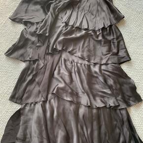 Sort nederdel fra Part Two, sort glat/skinnende stof, med læg/lag.  Lynlås i siden og elastik i taljen.  Mål: Talje: 44*2 ( men elastisk) Længde: 84