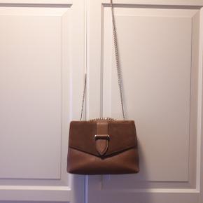 En eksklusiv taske i perfekt størrelse, som kan bruges både til hverdag og fest. Indvendigt har tasken to rum, som er adskilt af en lynlåslomme, samt en mindre lynlåslomme i det bagerste rum. Tasken lukkes med magnetlukning. Bagpå tasken er der desuden en lille lomme.  Tasken kan bæres som cross-body eller gøres dobbelt ved et enkelt træk og bæres på skulderen. En taske med mange anvendelsesmuligheder.  Mål:  Dybde 10 cm. Højde 19 cm. Bredde 23 cm.  Fremstår som ny og sælges kun til den rette pris.  Mp 1250 kr ekskl fragt.  Afhentning i Roskilde eller sender med DAO mod betaling af fragt.