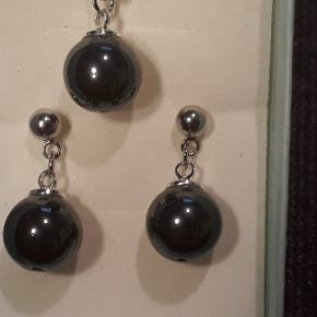 Eget design.  Smykkesæt i stål med sorte perler, måler 12 mm i diameter. Halskæden måler 42 cm, øreringene er 2.4 cm lange. Smykkesættet   leveres i gaveæsker og kan sendes for 10 kr med Post Nord, almenlig brev.
