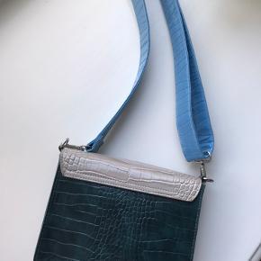 Hvisk taske brugt få gange. Blå/lysegrå/grøn. Remmen kan gøres længere. Har et stor og et lille rum. Prisen er fast. Køber betaler fragt eller den kan hentes ved Forum :-)