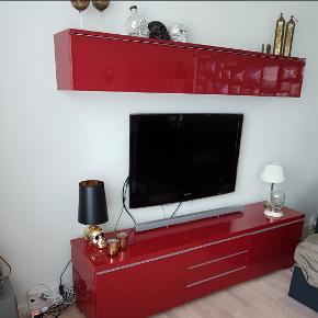 """Prisen er 1549 kroner.  Bestå Burs tv- og opbevarings møbler i rød højglans (fåes ikke længere).   Mål på tv skænk: L: 180cm D: 41cm H: 49cm  Mål på overskab(udvendige mål): L: 180cm D: 27cm H: 27,5cm  🌷Øverste del, indeholder 2 sideløbende rum til opbevaring. 🌷Nederste del indeholder 2 skuffer med tilhørende ekstra cd opbevaring(ialt 4 stk., se sidste billede) (eller hvad man ønsker de bruges til). Skufferne har hjul under hver. I midten er der 3 hylder (til fx. dvd, xbox el. lign.) med låger, så indholder ikke ses.  Jeg har sat standen som """"God, men brugt"""" - jeg har passet ret godt på det, så det har minimale brugsspor.  Nypris: ca. 3000 kroner.  ☝️ Indhold mv. medfølger (selvfølgelig) ikke 😉  🌸 SÅDAN HANDLER JEG 🌸  💙 BETALING VIA MOBILE PAY 💙 💚 Varen går til først betalende. 💛 Bytter/refunderer ikke/tager ikke varer retur. 🏠Hentes på Amager, tæt på Bella Center. 🚚Levering desværre ikke en mulighed, da vi ingen bil har.  VED AFHENTNING: Udlevering af vejnavn når du er på vej. Resten af adr. får du, når du er her. Bliver tit brændt af - på forhånd tak for forståelsen!🏡  Slået op flere steder."""