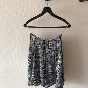 Mønstret top i sort og hvid med guldkæder som stropper