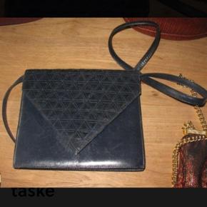 """Varetype: Clutch / Crossover Taske Håndtaske Skuldertaske fra Illums Bolighus. Størrelse: 21 x 18 cm Farve: Mørkblå / sortblå / Navy  Flot skindtaske med rem til skulder.   Remmen kan """"knappes af"""", så tasken kan anvendes som clutch / kuverttaske.   Med remmen på, kan den også benyttes som """"Cross Over"""".  Remmen er ca 105 cm lang Den er superfin - også indeni - og flot foret. Lidt """"negle ridser"""" ved lukning ellers helt perfekt og som ny. Købt i Illum / Illums Bolighus"""