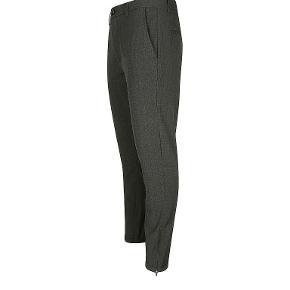 Gabba Pisa Chinos Cross Dark Grey med fin struktur. Buksen er med regular fit og kommer med lynlås detalje ved fodåbningerne. Benene leveres med opsmøg, som giver en cropped effekt. Fire lommer med slidsåbning. Spændes med lynlås og knap og kommer med bæltestropper. Let stretch. Kvalitet: 62% polyester, 33% viskose, 5% elastan.  Style: Pisa Chino Cross Dk. Grey B