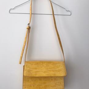Taske fra Pieces med justerbar strop.   Den er brugt en del og har derfor en lille skramme foran.   Tasken har et rum samt en lille lynlås lomme indvendigt.