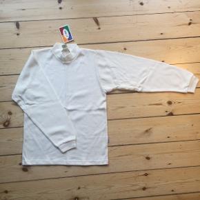 Natur/råhvid trøje med lange ærmer og turtleneck.Unisex. 100 % uld på ydersiden og 100% bomuld på indersiden. Vaskes ved 40 grader finvask. Helt ny og ubrugt med pris/mærkeseddel. Jeg har 6 stk. i str. 160. Ryglængde målt fra nederst på kraven: Cirka 56 cm. Pris pr. stk.: 50 kr. Eventuel fragt lægges oveni: Fragten bliver forholdsmæssigt billigere ved forsendelse af flere. 1 undertrøje vejer cirka 200 gram eksklusiv indpakning.