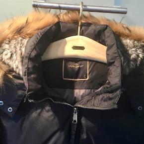 Virkelig lækker vinter frakke fra Soyaconcept. Ægte pels udenom hætten og fake indeni. Dun- / fjer-fyld. Elastisk bagpå i lænden. To lommer foran. Slidser med lynlås og tryklås i begge sider forneden. Indspænding med snor nederst bagpå.  Brystvidde : 2 x 57 cm. målt lige under ærmerne. Taljevidde : 2 x 51 cm. uden at strække elastikken som er i lænden.  Hoftevidde : 2 x 58 cm. Kun været på et par gange - har en anden favorit ... Farve: Sort Oprindelig købspris: 1500 kr. Sender gerne på købers regning : DAO 55,-