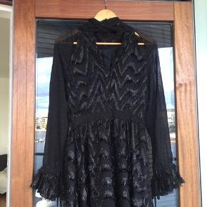 Kjolen er brugt én enkelt aften til en gallafest, så kjolen er i perfekt stand uden tegn på brug.  Kjolen er købt tilbage i 2018, og er fra AW18 kollektionen hos Stine Goya. Kjolen er lang, går ind i taljen, samt et bånd som man kan binde ved halsen. Alt i alt en super smuk og detaljeret kjole.